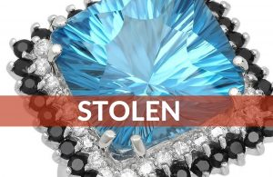 Stolen – Swiss Blue Topaz squared cushion cut with diamonds and blue sapphires adorning the stone, white gold